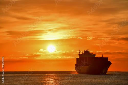 Spoed Fotobehang Oranje eclat Sunrise - Container ship entering Genoa Port December 2018