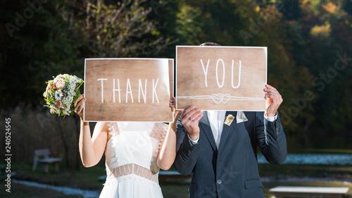 Valokuva  Hochzeitspaar mit Dankesschildern vor dem Gesicht für ihre Gäste