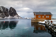 Lofoten Islands, Norway, Traditional Fishing House In A Fishing Village In Winter, Reflection In Water. Travel Norway.