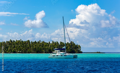 Lonely catamaran in the turquoise lagoon on the background of the island of Tahaa in the Leeward group of the Society Islands of French Polynesia Fototapete