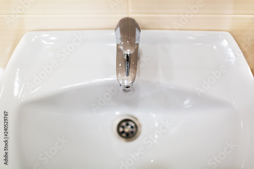 Fotomural  White sink or wash basin with shiny chromed faucet against the background of  wall