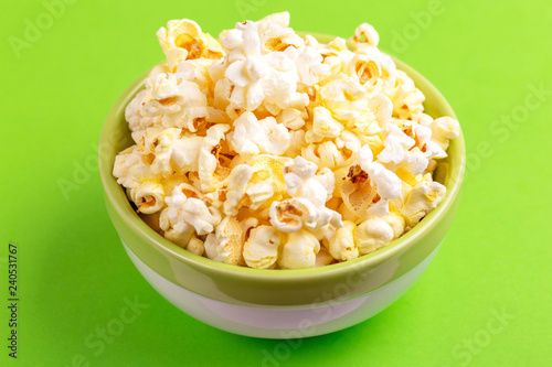 Photo  Tasty salty popcorn in bowl on bright green backgraund