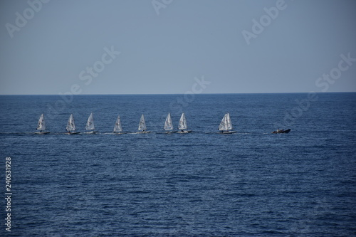 Fotografie, Obraz Fia di barchette a vela trainate da un motoscafo prima di una regata