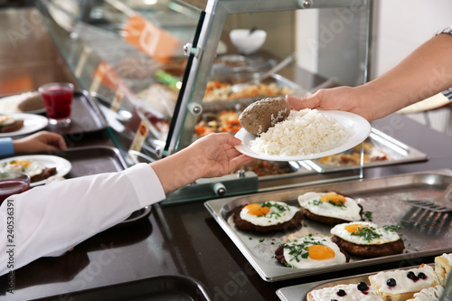 Woman giving plate with healthy food to girl in school canteen, closeup