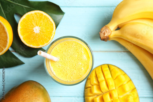 Glass of fresh mango drink and tropical fruits on color wooden background, top view