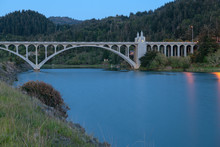 The Rogue River Bridge With The Obelisk Illuminated At Sunset In Gold Beach, Oregon, USA