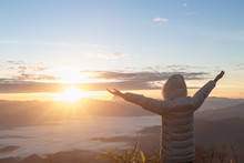 Christian Woman  Hands Praying To God On The Mountain Background With Morning Sunrise, Carefree Happy Woman Enjoying Nature  On Top Of Mountain Cliff With Sunrise.