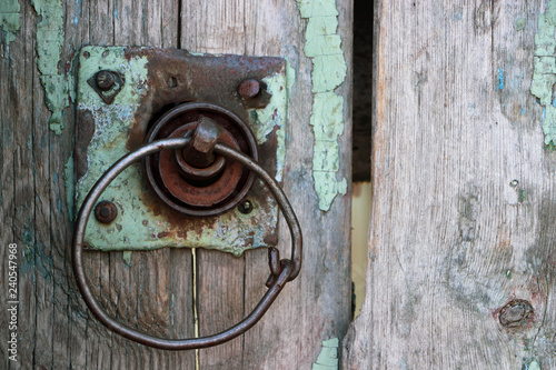 An old wooden gate with a round rusty handle. Close-up.