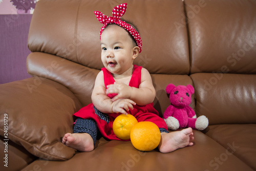 Asian girl in red dress Sit on a brown sofa. Hold orange in hand. Good mood and happy