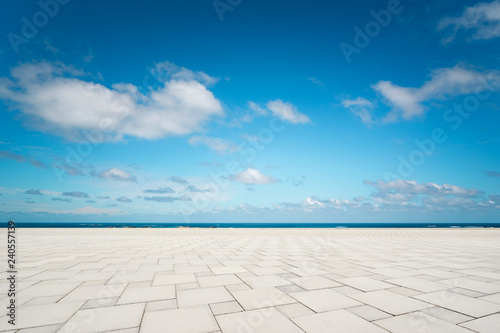 Outdoor empty square marble floor and sea under the blue sky .