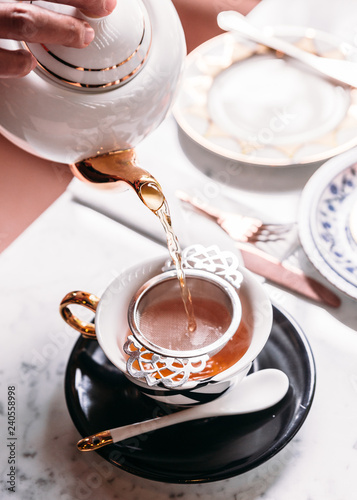 Vászonkép  Hot Apple Tea served by pouring from mug through stainless steel tea strainer infuser in porcelain vintage cup