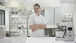 Portrait of a happy young trainee chef or worker in a commercial kitchen. Woman is posing in the kitchen with wire whisk
