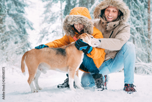 Fotografía  Father and son; dressed in Warm Hooded Casual Parka Jacket Outerwear walking with their beagle dog; they petting him and smiling in snowy forest