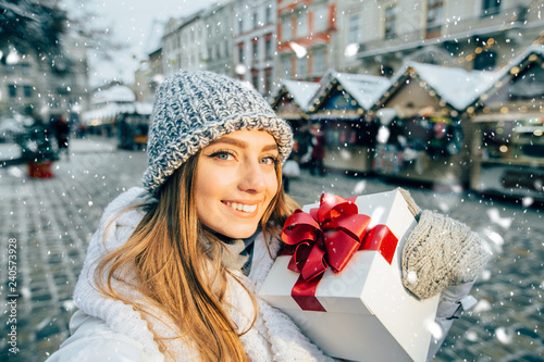 Valokuvatapetti Portrait of playfull positive young woman toothy smiling, holding gifts with red bow, making selfie, looking at camera at Christmas fair in evening