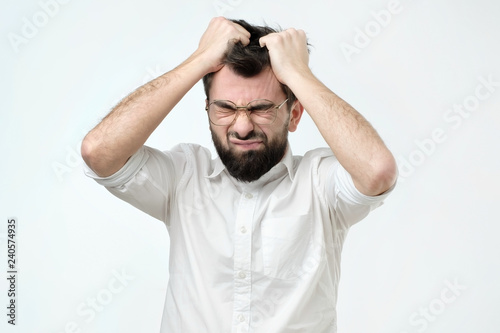 Obraz Enraged young businessman pulling his hair out for exasperation, having a burnout at work, screaming for frustration and stress - fototapety do salonu