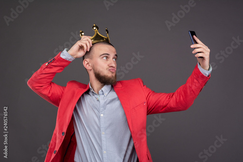 Young bearded handsome man in gold crown taking selfie looking at smartphone Poster Mural XXL