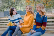 canvas print picture - Cheerful attractive three young women best friends having fun and drink coffee together outside.