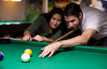 Handsome Guy And A Beautiful Girl Are Playing Billiards