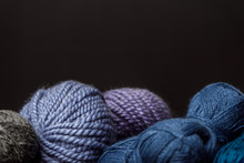 Close Up View Of Purple, Blue And Grey Yarn Balls On Black Backdrop