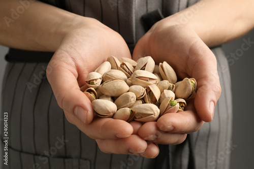 Woman holding organic pistachio nuts on grey background, closeup