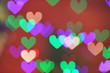 Blurred view of beautiful heart shaped lights on color background