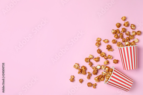 Overturned paper cups with caramel popcorn on color background, top view. Space for text