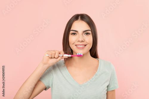 Fotografía Beautiful woman brushing teeth on color background
