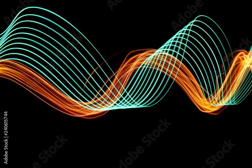 Long exposure, light painting photography. Green and vibrant metallic yellow gold, parallel lines of vibrant color, curving and wavy lines against a black background