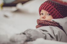 Funny Little Child Girl Wearing In Red Hat, A Scarf, And A Warm Winter Suit With Gloves Having Fun At Winter Day In Beautiful Winter Park Playing With Snow