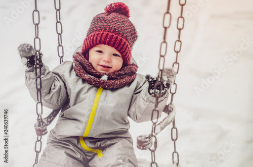 Fotografía  Funny child wearing in red hat, a scarf, and a warm winter suit with gloves having fun at winter day riding on a swing on playground