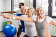 happy senior multiethnic sportspeople synchronous exercising at sports hall
