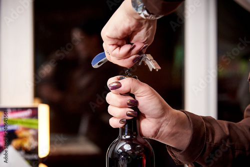 Fotografie, Obraz  Girl opens a bottle of wine with a corkscrew close-up.