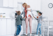 Tired Mother With Infant Kid Cooking While Naughty Children Playing In Kitchen