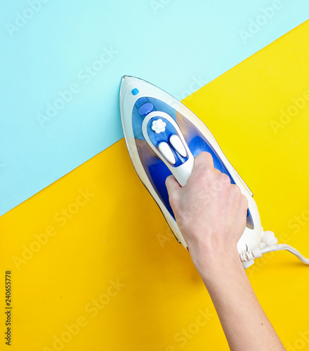 Stampa su Tela Top view, minimalism, female hand holding an iron on a pastel yellow-blue backgr