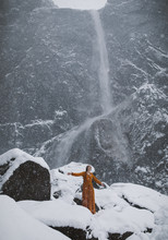 Woman In Dress In Front Of Yosemite Falls During A Snow Storm
