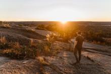 Man In Hat Walking In A Desert At Sunset