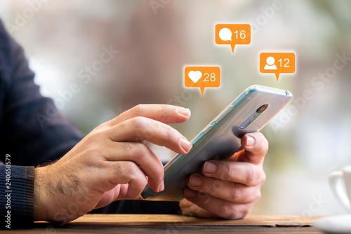 Fotografie, Obraz  Man Checking His Social Media Account Using Smart Phone