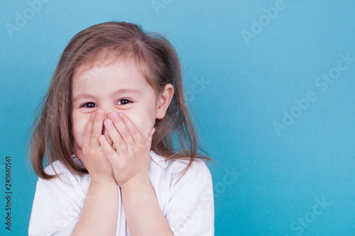 Fotografie, Obraz  Little girl on a blue background laughs covering her face with her hands