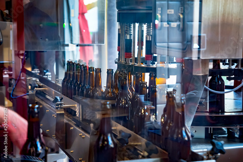 Foto op Canvas Bier / Cider Full beer glass bottles moving on a conveyor line