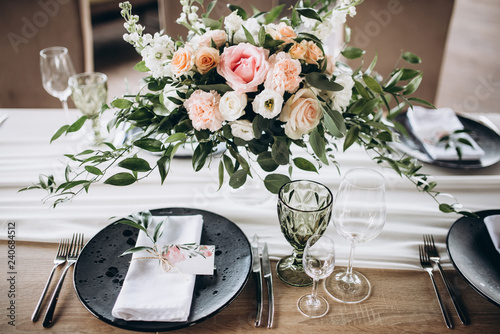 Obraz Wedding table serving. Wedding banquet. Beautiful festive table decorated with bouquet of flowers, black plate with card of name guest and cutlery. Top view - fototapety do salonu