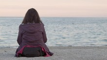 4K The Woman Sits On The Beach...