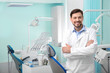 Professional male dentist in white coat at workplace. Space for text