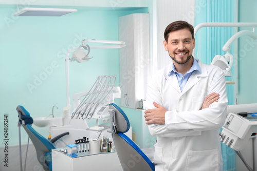fototapeta na lodówkę Professional male dentist in white coat at workplace. Space for text