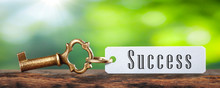 Old Brass Key And Tag With The Word Success On Wooden Table With Green Background - Business / Financial Success Concept