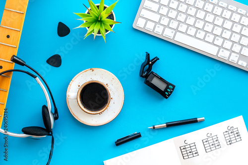 Fototapeta Headphone with paper note, keyboard and coffee in music studio for dj or musician work blue background top view obraz na płótnie