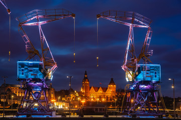 FototapetaIlluminated old port cranes on a boulevard in Szczecin City at night