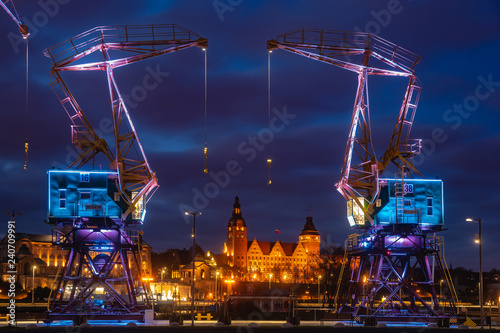 Foto Illuminated old port cranes on a boulevard in Szczecin City at night