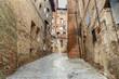 Medieval narrow street Vicolo del Tone in Siena, Tuscany, Italy.