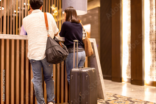 Fotografering  Asian couple with suitcase checking in at hotel reception.