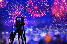 Back Side Silhouette Digital Camera On Tripod Recording Beautiful Fireworks For Celebrate In Low Light